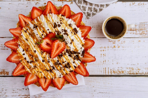 Café e strawberey com torta de creme chantilly na superfície branca