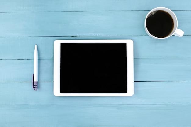 Café e tablet com caneta em fundo azul