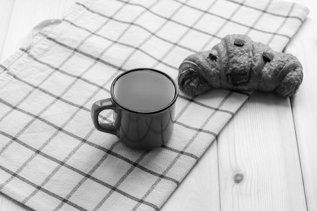 Café e um croissant em um fundo de madeira. visto de cima. grão de café