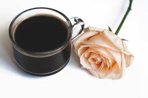 Café e uma rosa amarela em um fundo branco