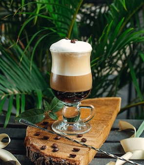 Café em camadas com creme e grãos de café na placa de madeira rústica