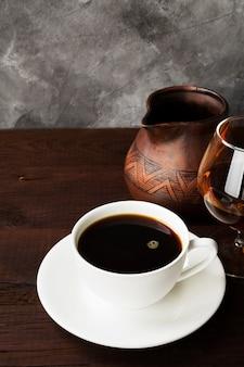 Café em copo branco com conhaque e argila cezve na mesa de madeira