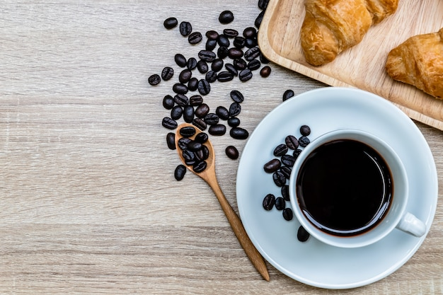 Café em copo branco com grão de café e croissants na mesa de madeira, conceito de café da manhã