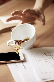Café em copo branco, derramando sobre a mesa no dia útil da manhã na mesa de escritório