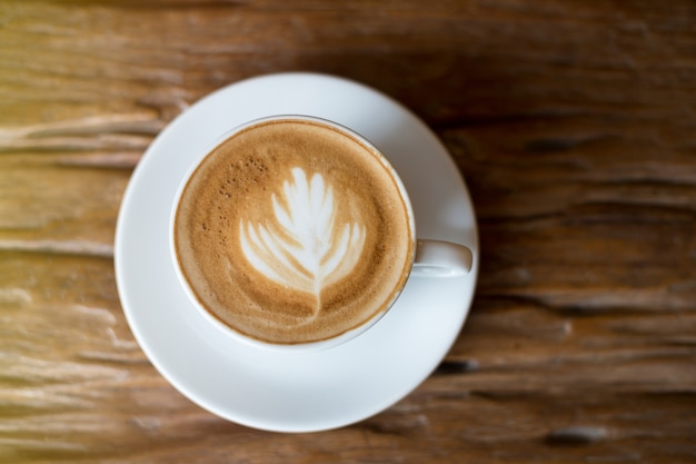 Café em copo branco na mesa de madeira