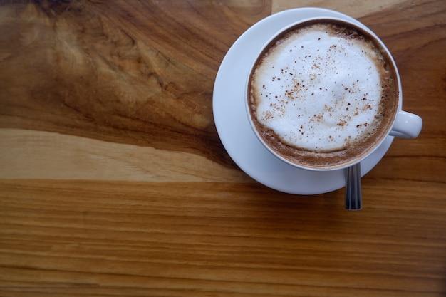 Café em copo branco na mesa de madeira.