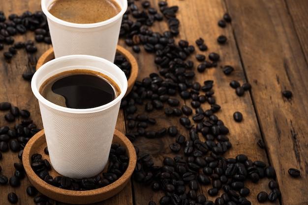 Café em copo de papel na madeira