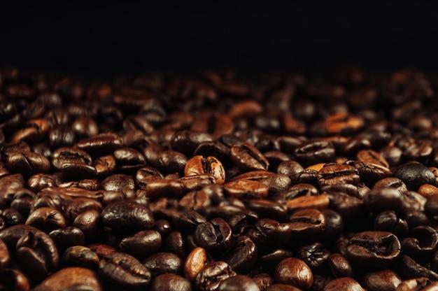 Café em grão close-up. o conceito de fazer café forte aromático em um fundo preto em um tom discreto. fotografia discreta.