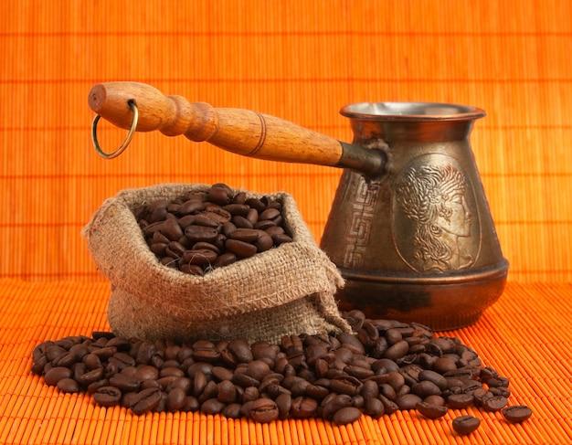 Café em grão e cafeteira de cobre