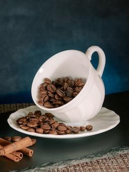 Café em grão torrado, com paus de canela em uma caneca de cerâmica branca, na parede azul, meia vista, macro vertical, close-up