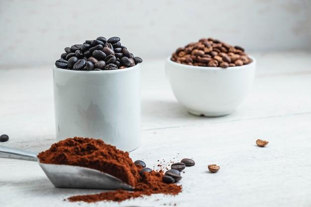 Café em pó e grãos de café na mesa branca