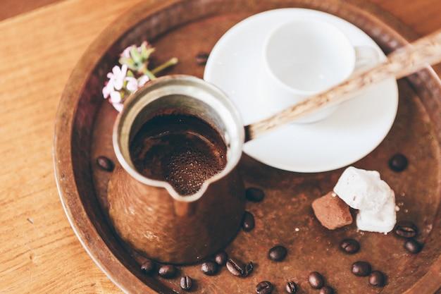 Café em um café marrom cobre e uma xícara de cerâmica branca em uma bandeja com grãos de café