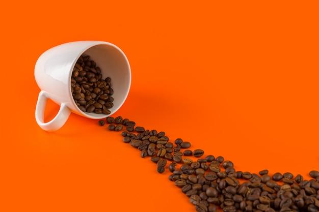 Café em um copo branco sobre um fundo laranja com grãos de café.