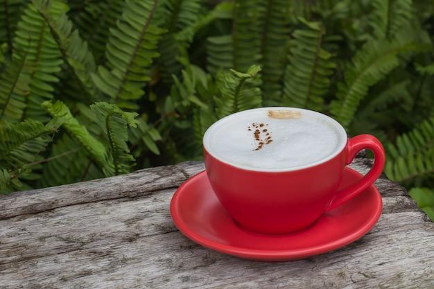 Café em um copo vermelho sobre uma mesa de madeira