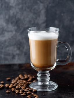 Café em um fundo escuro com grãos de café torrados