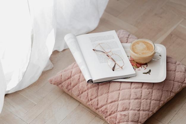 Café em uma almofada de veludo rosa com uma revista aberta