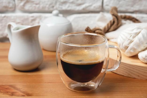 Café em uma caneca de vidro em uma mesa de madeira contra uma parede de tijolos brancos.