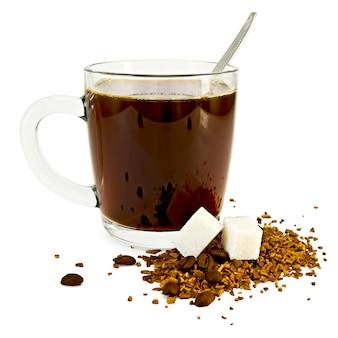 Café em uma caneca de vidro, uma colher, grãos e grânulos de café em uma mesa com dois torrões de açúcar isolados no fundo branco
