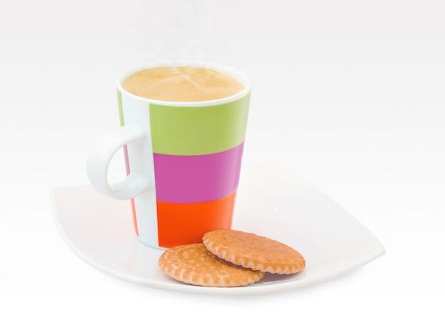 Café em uma divertida caneca multi colorida em um pires e dois biscoitos
