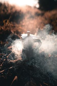 Café em uma panela moka em uma fogueira de acampamento pela manhã, café da manhã