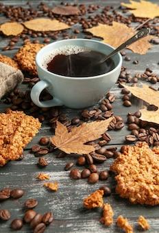 Café em uma xícara azul. biscoitos de aveia caseiros estão disponíveis nas proximidades.