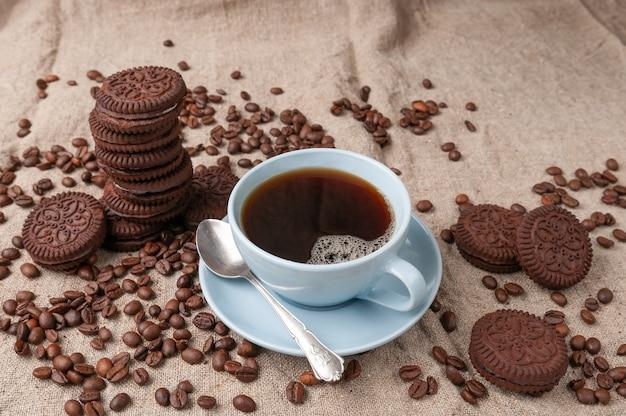 Café em uma xícara azul. biscoitos de chocolate próximos.