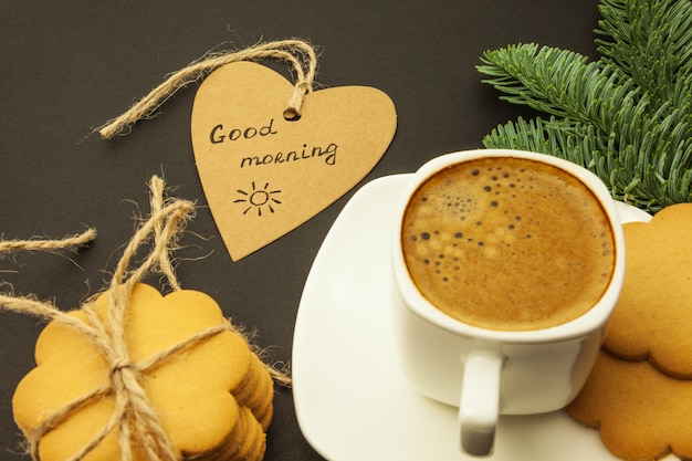 Café em uma xícara branca, coração com uma inscrição bom dia