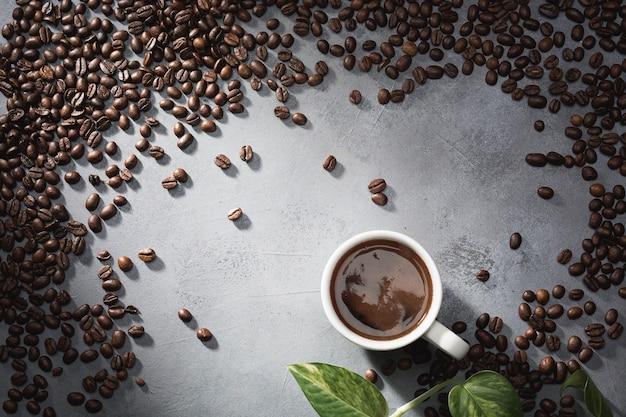 Café em uma xícara branca e grãos de café em cima da mesa.