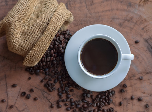 Café em uma xícara branca e grãos de café em uma mesa de madeira