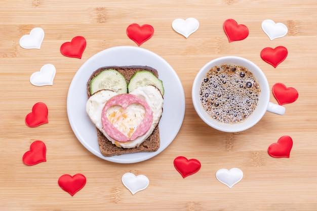 Café em uma xícara branca e um sanduíche com ovos fritos em forma de coração, salsichas e pepinos em um prato verde