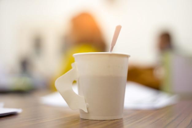 Café em uma xícara branca em cima da mesa.