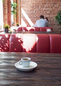 Café em uma xícara branca fica em uma mesa de madeira
