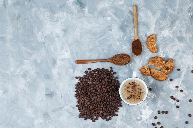 Café em uma xícara com biscoitos, grãos de café, vista superior do café moído em um fundo cinza sujo