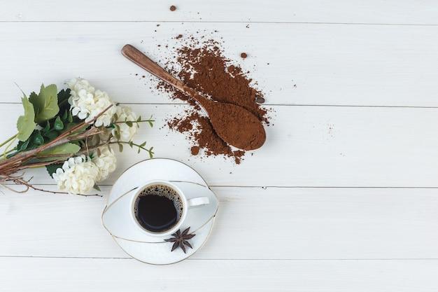 Café em uma xícara com café moído, especiarias e flores, vista superior em um fundo de madeira