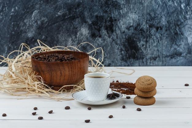 Café em uma xícara com café moído, grãos de café, especiarias, vista lateral de biscoitos em fundo de madeira e grunge