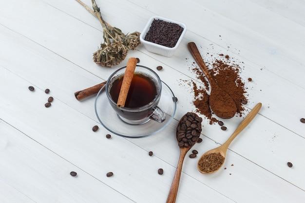 Café em uma xícara com café moído, grãos de café, paus de canela e ervas secas, vista de alto ângulo em um fundo de madeira