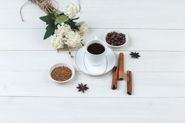 Café em uma xícara com grãos de café, especiarias, flores, vista de alto ângulo de café moído em um fundo de madeira