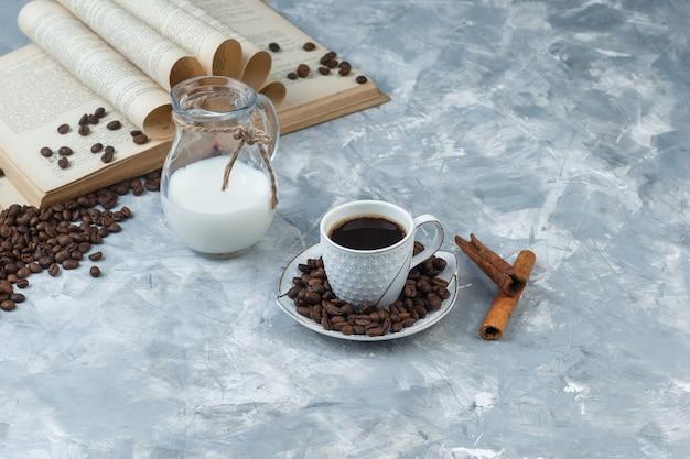 Café em uma xícara com grãos de café, livro, paus de canela, visão de alto ângulo do leite em um fundo de gesso cinza