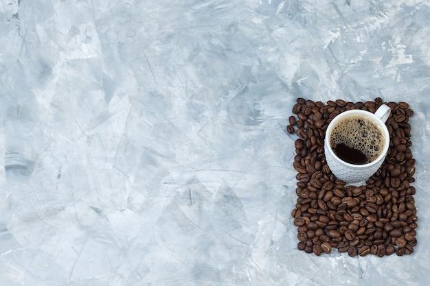 Café em uma xícara com grãos de café sobre um fundo de mármore azul