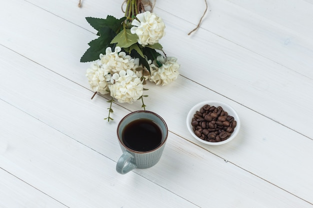 Café em uma xícara com grãos de café, vista de alto ângulo de flores em um fundo de madeira