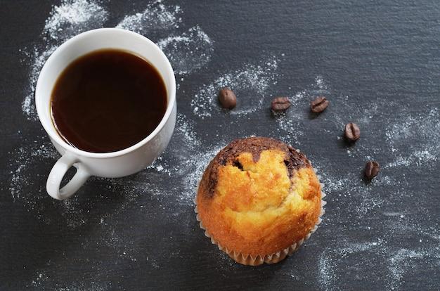 Café em uma xícara com um bolinho em um fundo de pedra preta