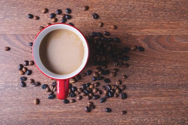 Café em uma xícara de café vermelho na mesa de madeira