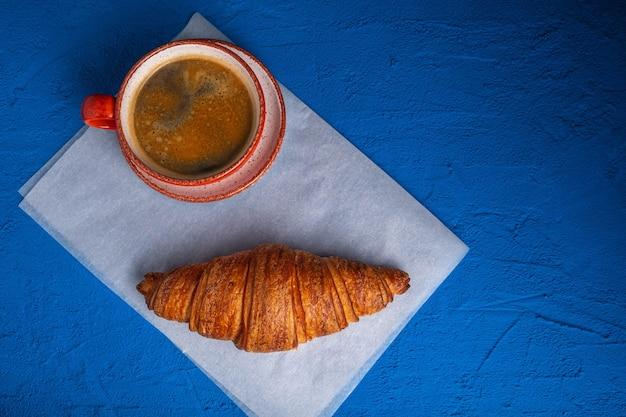 Café em uma xícara e croissant em uma mesa azul