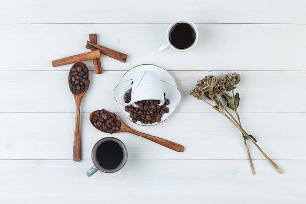 Café em xícaras com grãos de café, paus de canela e ervas secas, vista superior em um fundo de madeira