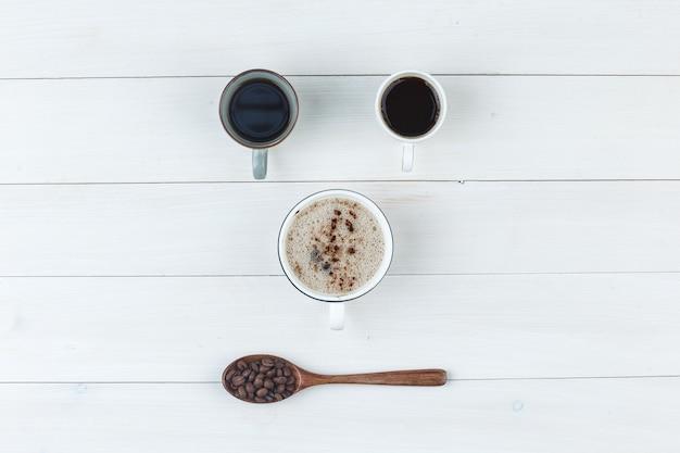 Café em xícaras com vista superior dos grãos de café em um fundo de madeira