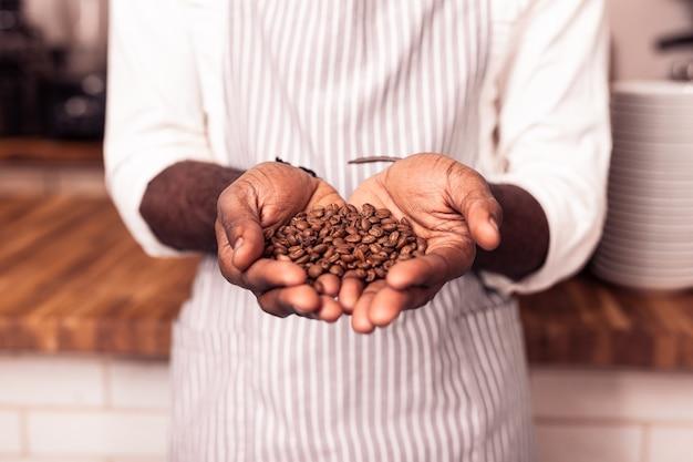 Café especial. um bom barista profissional segurando grãos de café torrados enquanto os mostra a você