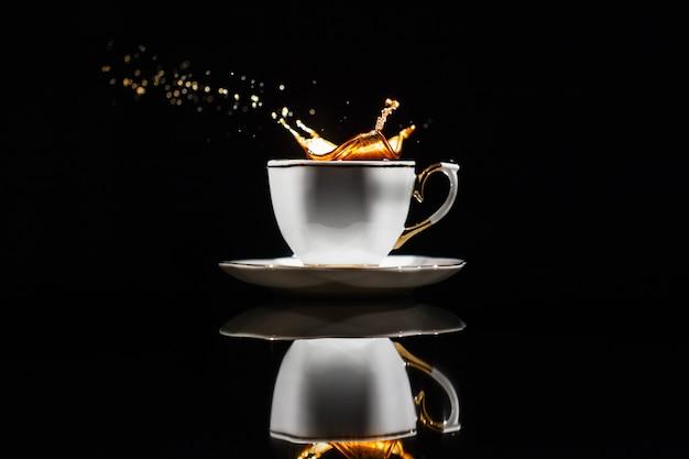 Café espirra no copo branco no fundo preto