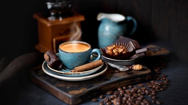 Café expresso com canela em pau. xícara de café azul em uma placa de madeira, grãos de café