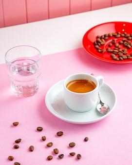 Café expresso com copo de água e grãos de café na mesa