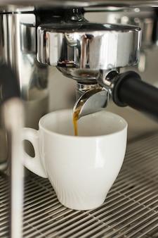 Café expresso derramando da máquina de café em um copo